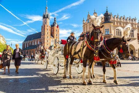KRAKOW, POLAND - JUNE 16, 2014: Horse carriages at main square in Krakow in a summer day, Poland on June 16, 2014