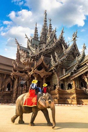 Tourists ride elephant around the Sanctuary of Truth in Pattaya, Thailand in a summer day