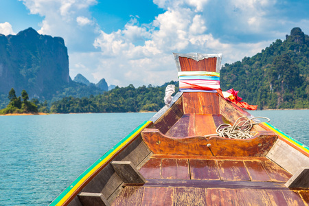 Wooden thai traditional long tail boat on Cheow Lan lake, Ratchaprapha Dam, Khao Sok National Park in Thailand in a summer day