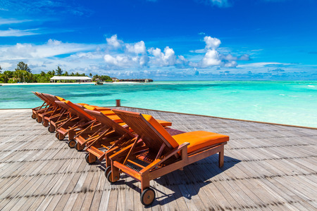 MALDIVES - JUNE 24, 2018: Wooden sunbed on tropical beach in the Maldives at summer day