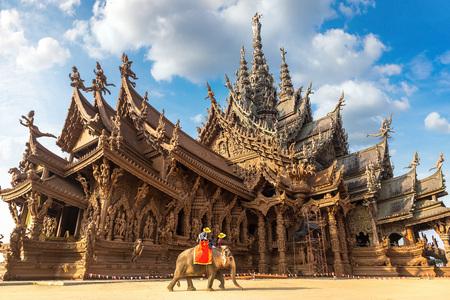 Touristen reiten an einem Sommertag Elefanten um das Heiligtum der Wahrheit in Pattaya, Thailand Standard-Bild