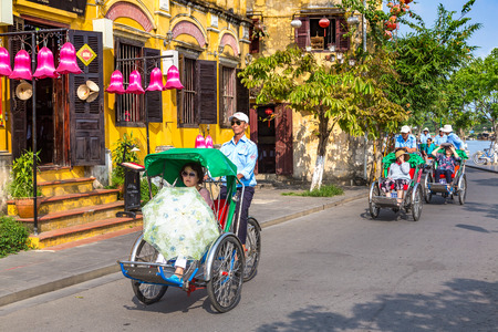 HOI AN, VIETNAM - JUNE 8, 2018: Traditional Ð¡yclo rickshaw drivinge in Hoi An, Vietnam in a summer day