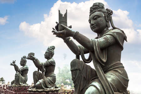 Buddhist statues praising near Giant Buddha in Hong Kong at summer day