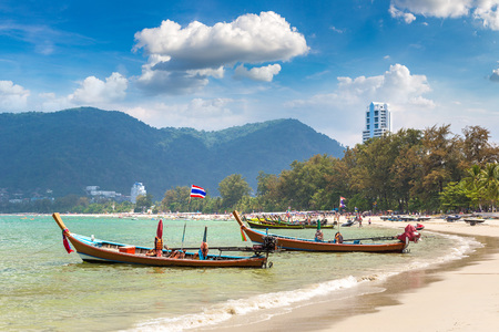 Traditional long tail boat on Patong beach and Andaman sea on Phuket in Thailand in a summer day
