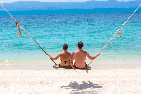 Young couple swinging on a swing on Koh Samui island, Thailand in a summer day