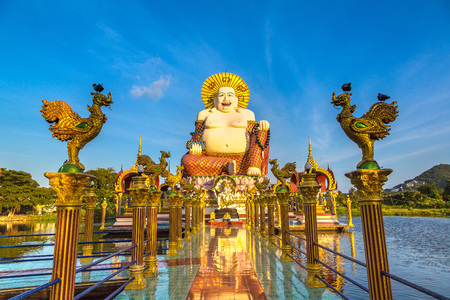Giant smiling or happy buddha statue in Wat Plai Laem Temple, Samui, Thailand in a summer day Stock Photo