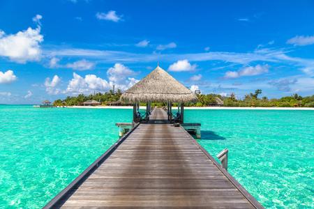 MALDIVES - JUNE 24, 2018: Water Villas (Bungalows) and wooden bridge at Tropical beach in the Maldives at summer day