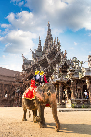 Tourists ride elephant around the Sanctuary of Truth in Pattaya, Thailand in a summer day 免版税图像