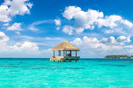 MALDIVES - JUNE 24, 2018: Water Villas (Bungalows) and wooden bridge at Tropical beach in the Maldives at summer day Редакционное