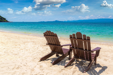 Empty wooden chairs on a sandy beach on Koh Samui island, Thailand in a summer day Imagens