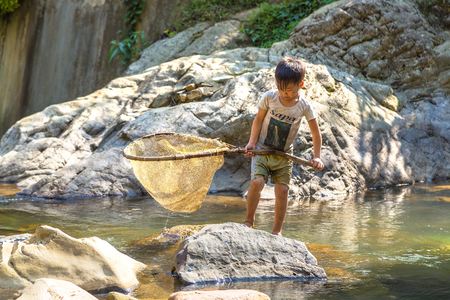 SAPA, VIETNAM - JUNE 19, 2018: Boy fishing at the river in Sapa, Lao Cai, Vietnam in a summer day