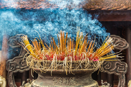 Burning incense sticks in Tran Quoc pagoda in Hanoi, Vietnam in a summer day