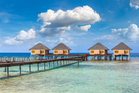 MALDIVES - JUNE 24, 2018: Water Villas (Bungalows) and wooden bridge at Tropical beach in the Maldives at summer day Redakční