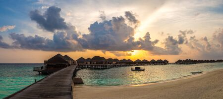 Panorama of Tropical sunset over bungalows at Tropical beach in the Maldives at summer evening 免版税图像