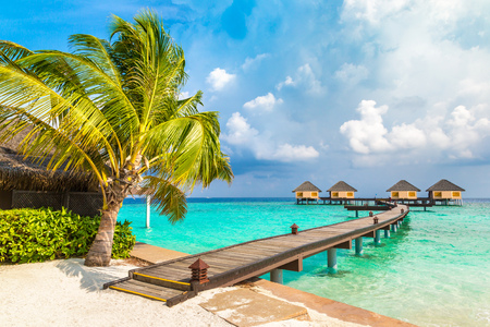 MALDIVES - JUNE 24, 2018: Water Villas (Bungalows) and wooden bridge at Tropical beach in the Maldives at summer day 新聞圖片
