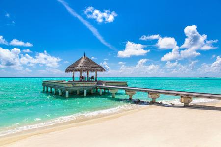 Malediwy - 24 czerwca 2018 r.: Water Villas (Bungalows) i drewniany most na tropikalnej plaży na Malediwach w letni dzień