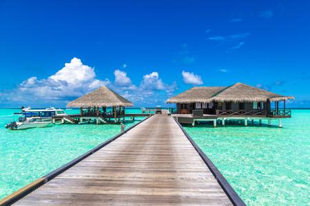 MALDIVES - JUNE 24, 2018: Water Villas (Bungalows) and wooden bridge at Tropical beach in the Maldives at summer evening