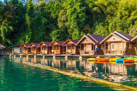 Traditional Thai bungalows at Cheow Lan lake, Ratchaprapha Dam, Khao Sok National Park in Thailand in a summer day