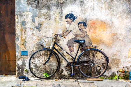 """PENANG, MALAYSIA - FEBRUARY 22, 2020: Famous Mural graffiti of """"little children on a bicycle"""" by Lithuanian artist Ernest Zacharevic in Georgetown, Penang, Malaysia"""