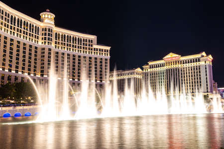 LAS VEGAS, USA - MARCH 29, 2020: Fountains of Bellagio at Bellagio Hotel and Casino and Caesars Palace at night in Las Vegas, Nevada, USA