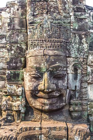 Stone faces of Bayon temple is Khmer ancient temple in complex Angkor Wat in Siem Reap, Cambodia in a summer day