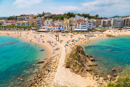 BLANES, SPAIN - JUNE 26, 2016: Tourists enjoy at the beach in Blanes in Costa Brava in a beautiful summer day, Spain Редакционное