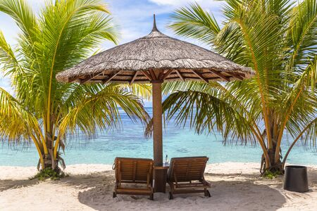 Wooden sunbed and umbrella on tropical beach in the Maldives at summer day