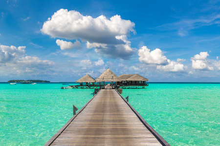 Water Villas (Bungalows) and wooden bridge at Tropical beach in the Maldives at summer day Redactioneel