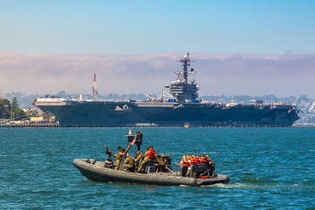 SAN DIEGO, USA - MARCH 29, 2020: Naval Base navy guard boat patrol against modern nuclear aircraft carrier in San Diego, California, USA