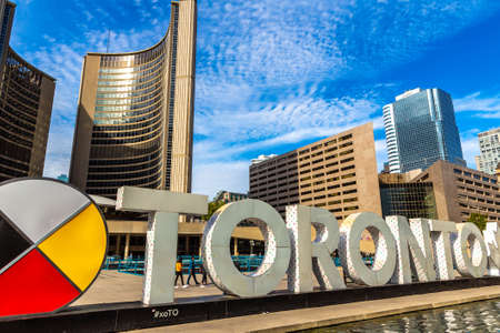 TORONTO, CANADA - APRIL 2, 2020: Toronto sign and city hall at Nathan Phillips Square in Toronto in a sunny day, Ontario, Canada