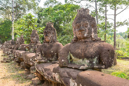 Row of sculptures in the Gate of in complex Angkor Wat in Siem Reap, Cambodia in a summer day Banque d'images