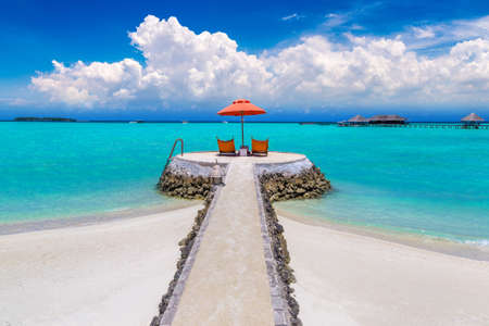 MALDIVES - JUNE 24, 2018: Wooden sunbed and umbrella on tropical beach in the Maldives at summer day