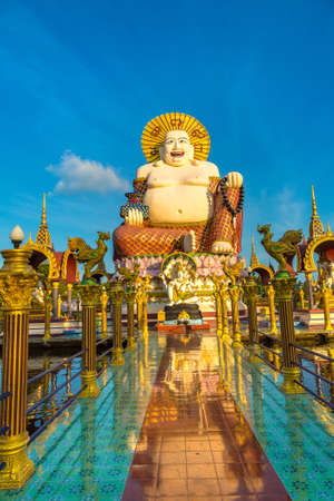Giant smiling or happy buddha statue in Wat Plai Laem Temple, Samui, Thailand in a summer day Banque d'images