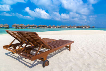 Wooden sunbed on tropical beach in the Maldives at summer day