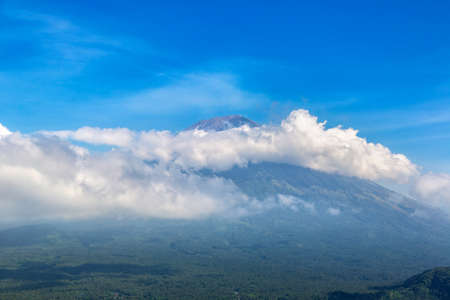 Beautiful view at active volcano mount Agung surrounding clouds on Bali, Indonesia in a sunny day Фото со стока