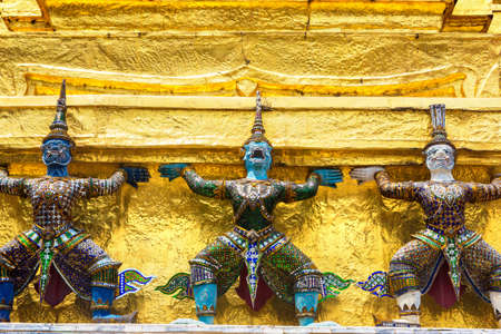 Demon Guardian Statues are supporting golden Chedi stupa at Wat Phra Kaew temple in a sunny day