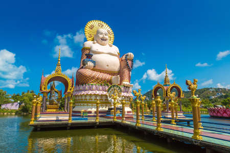Giant smiling or happy buddha statue in Wat Plai Laem Temple, Samui, Thailand in a summer day Фото со стока