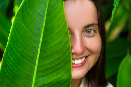 Beautiful woman hiding behind the big tropical leaf