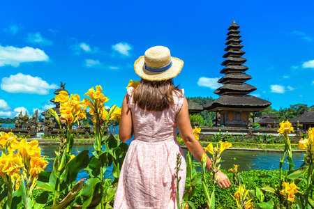 Woman traveler at  Pura Ulun Danu Beratan Bedugul temple on a lake in Bali, Indonesia Standard-Bild