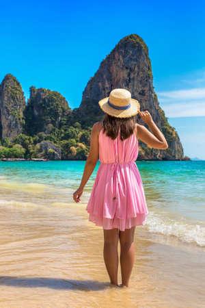 Young beautiful woman wearing pink dress and straw hat at tropical Railay Beach, Krabi, Thailand Standard-Bild