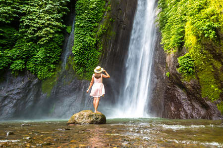 Woman traveler at  Munduk waterfall in Bali, Indonesia in a sunny day