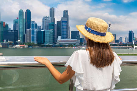 Woman traveler looking at Singapore cityscape in a sunny day in Singapore