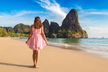 Young beautiful woman wearing pink dress and a wreath of flowers at tropical Railay Beach, Krabi, Thailand Standard-Bild