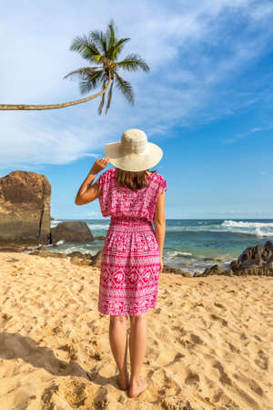 Portriat of young beautiful woman wearing a hat and red dress staying on a tropical beach near sea
