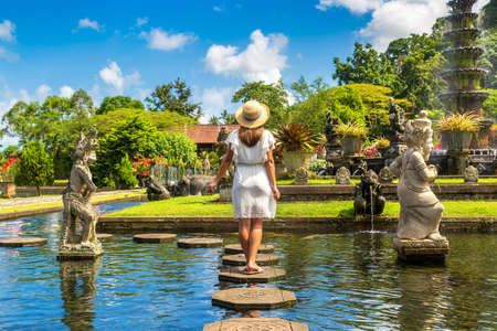Woman traveler wearing white dress and straw hat at  Taman Tirtagangga temple on Bali, Indonesia in a sunny day