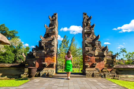 Woman traveler at Traditional entrance gate to Taman Ayun Temple on Bali, Indonesia in a sunny day Standard-Bild