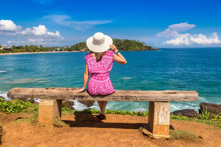 Woman seatted on a bench at Mirissa tropical Beach in a sunny day in Sri Lanka