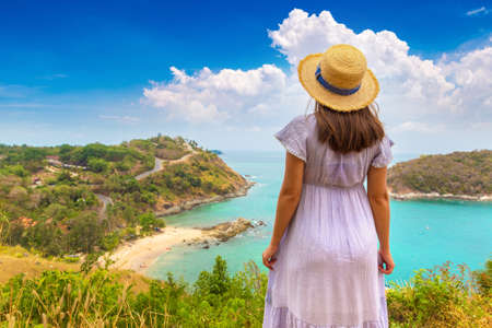 Woman traveler wearing blue dress and straw hat at   Panoramic view of  Yanui Beach at Phuket in Thailand in a summer day