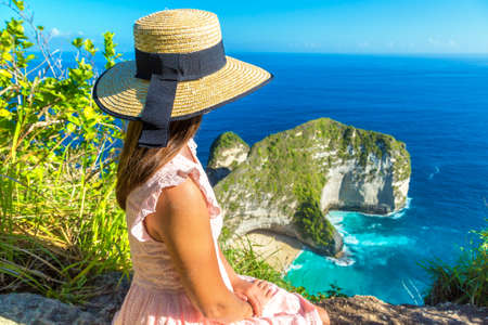 Woman traveler at  viewpoint at Kelingking Beach in Nusa Penida island, Bali, Indonesia