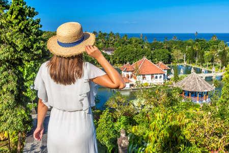 Woman traveler at Panoramic view of Karangasem Taman Ujung, Water Palace on Bali, Indonesia in a sunny day